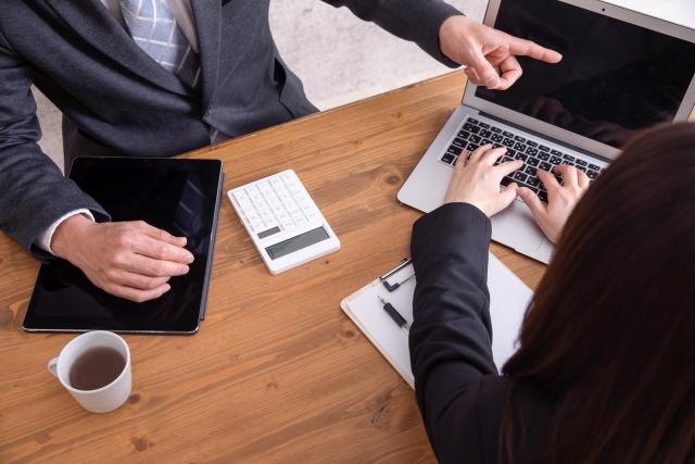 ノートパソコンを見ながらミーティングをする二人のビジネスパーソン